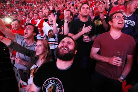 Michael Perrone sings the national anthem with fellow Chicago Blackhawks fans before Game 5 of the Stanley Cup Final at the United Center.