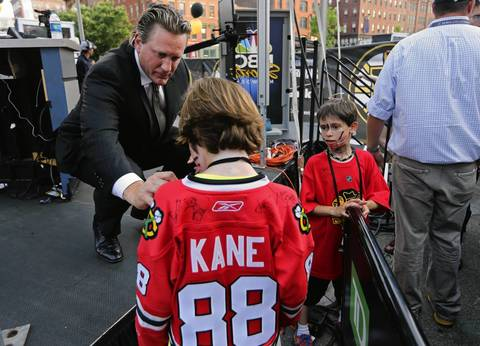 Former Blackhawks player Jeremy Roenick sign the jersey for 9-year-old Gianni Baglivo.