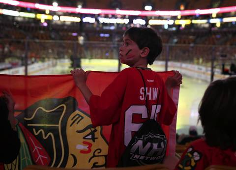 Chicago Blackhawks fan Noah Geisen, 8, of Chicago holds a Hawks flag before the team plays the Boston Bruins in Game 6 of the NHL Stanley Cup Final at the TD Garden in Boston.
