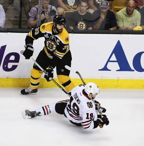 Jonathan Toews goes down after colliding with the Bruins' Zdeno Chara during the first period.