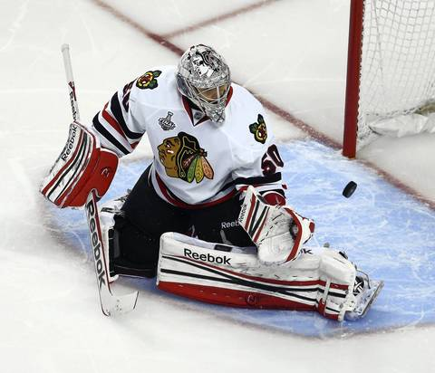 The puck bounces out of the glove of goalie Corey Crawford after he makes a save during the first period.