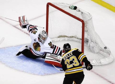 The Bruins' Chris Kelly scores a goal past goalie Corey Crawford during the first period.