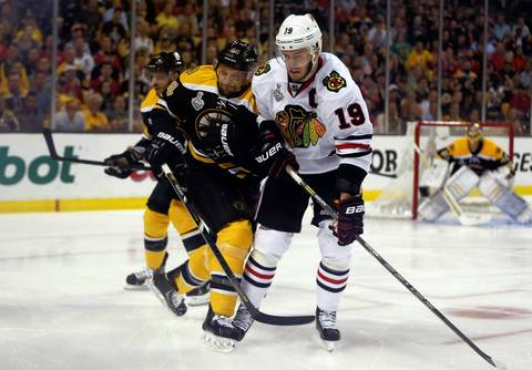 Jonathan Toews and the Bruins' Dennis Seidenberg collide in the first period.