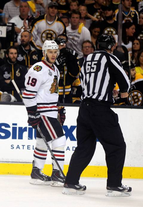 Jonathan Toews talks with linesman Pierre Racicot in the first period.