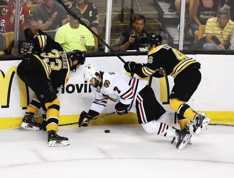 Brent Seabrook goes down, courtesy of the Bruins' Zdeno Chara and David Krejci during the first period.