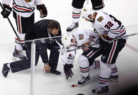 Andrew Shaw is taken off the ice after taking a puck to the face in the first period.