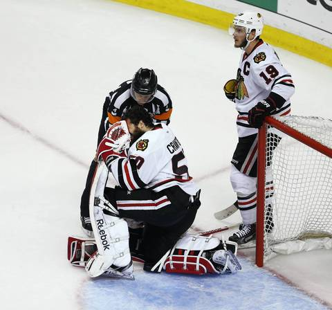 Goalie Corey Crawford holds his face after he lost his helmet.
