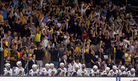 The Blackhawks bench watches as the Bruins fans celebrate a first-period goal by Chris Kelly.