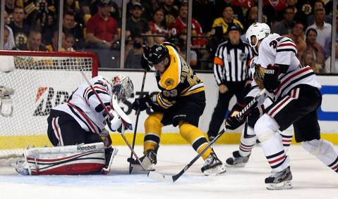 Blackhawks goalie Corey Crawford stops a shot by the Bruins' Brad Marchand as Michal Rozsival trails the play.