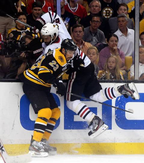Johnny Oduya hits the boards hard as the Bruins' Chris Kelly closes in.