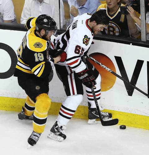 With blood dripping down the side of his face, a helmet-less Andrew Shaw controls the puck away from the Bruins' Tyler Seguin during the second period.