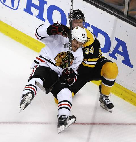 Andrew Shaw is dragged down by the Bruins' Carl Soderberg during the third period.