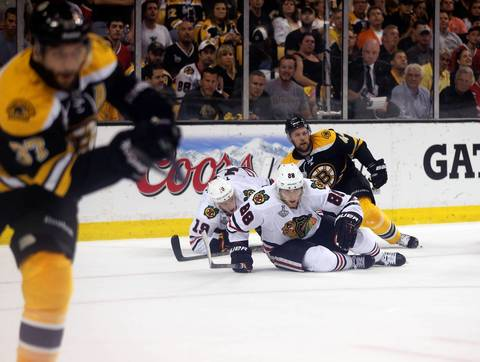 Patrick Kane, Jonathan Toews and the Bruins' Dennis Seidenberg hit the ice in the third period.