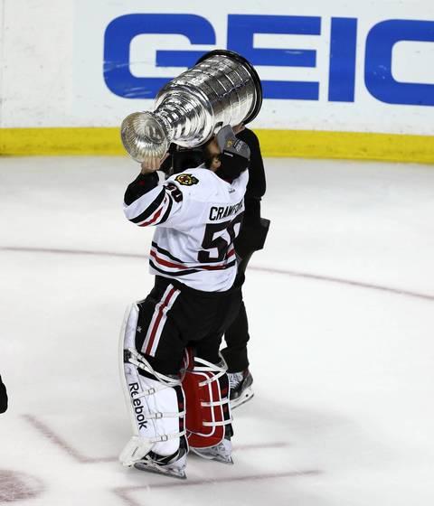 Blackhawks goalie Corey Crawford hoists the Cup.
