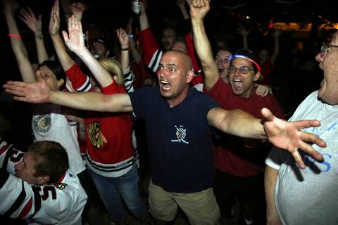 Jason Lontoc reacts as the Blackhawks win the Stanley Cup after beating the Boston Bruins while watching the game at David Gibson's front yard party on Kenneth and Byron avenues in the Old Irving Park neighborhood of Chicago.