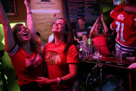 Two bartenders celebrate the Blackhawks Stanley Cup victory at the Third Rail Tavern on Madison in Chicago.