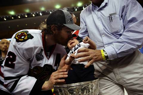 Duncan Keith kisses his baby in the Stanley Cup.