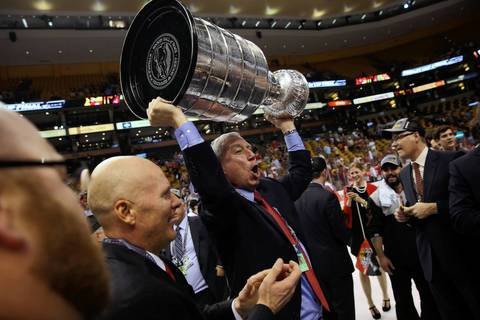 Blackhawks president and CEO John McDonough lifts the Stanley Cup.
