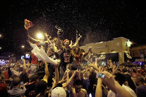 Crowds dance on an SUV and spray beer in the air near Clark Street and Sheffield Avenue as they celebrate the Chicago Blackhawks winning the Stanley Cup.