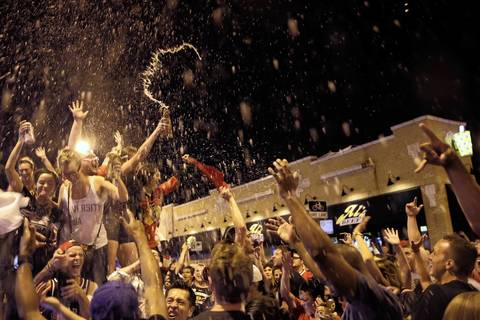 Crowds dance on an SUV and spray beer in the air at Clark Street and Sheffield Avenue as they celebrate the Chicago Blackhawks winning the Stanley Cup.