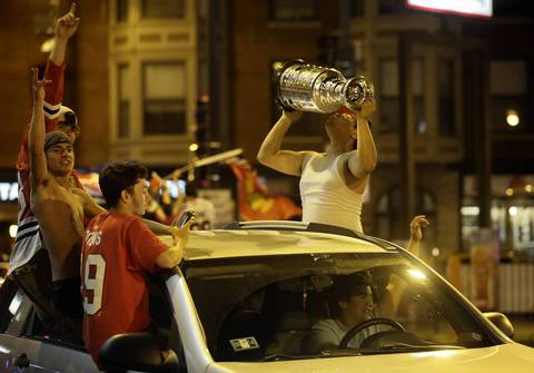 Julio Gonzalez, 16, of Chicago, holds a replica Stanley Cup while celebrating on Clark Street in Wrigleyville after the Blackhawks beat the Boston Bruins.