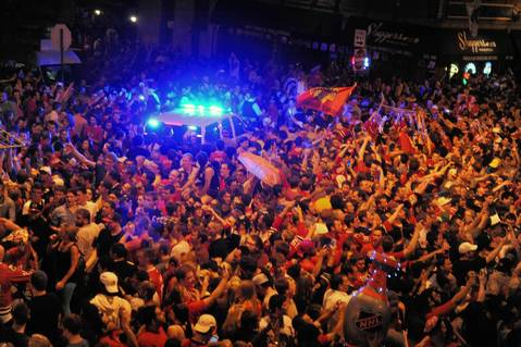 A police vehicle is surrounded by fans on North Clark Street celebrating the Chicago Blackhawks victory in the Stanley Cup Final.