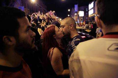 Tiffany Grivas and Jerry Bassett of Chicago, share a kiss as crowds fill Clark Street and Sheffield Avenue celebrating the Blackhawks winning the Stanley Cup.