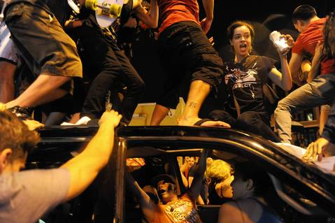 Fans climb on top of a vehicle as they react on N. Clark Street to the Chicago Blackhawks' victory in the Stanley Cup Final.