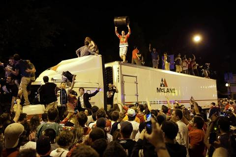 Crowds climb on a semi-trailer on Clark Street near Sheffield Avenue as they celebrate the Blackhawks winning the Stanley Cup.