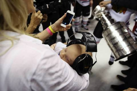 Duncan Keith's son Colton is held by his wife Kelly-Rae as the Hawks celebrate.