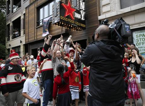 Blackhawks fans cheer for a television news camera outside the Pony Inn at 1638 W. Belmont Ave. in Chicago to celebrate the Stanley Cup Championship.