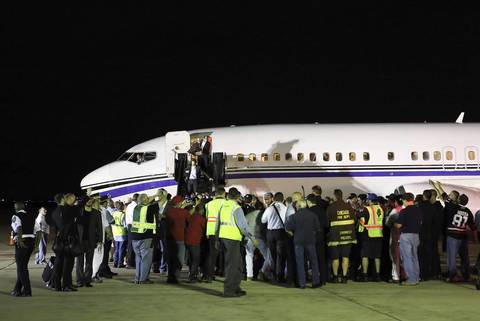 City employees gather as the Blackhawks get off a chartered plane after arriving at O'Hare International Airport at about 4:20 a.m., the morning after the Blackhawks won the Stanley Cup Final trophy