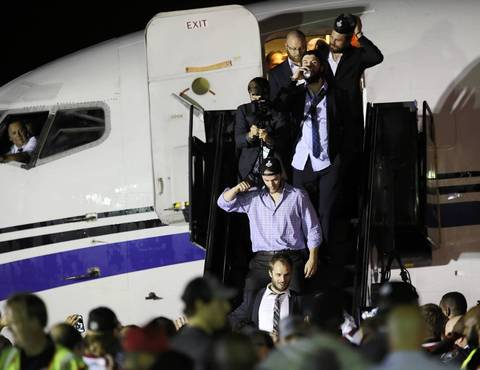 Blackhawks players exit a chartered plane after arriving at O'Hare International Airport at about 4:20 a.m. Tuesday.