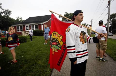 Michael Lev, 17, of Lombard, carries the flag while joining several hundred fans outside the York Tavern in Oak Brook who are waiting for Blackhawks coach Joel Quenneville to make an appearance. The coach lives nearby in Hinsdale and frequents the York.