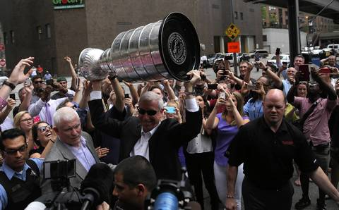 President and CEO John F. McDonough, (sunglasses) of the Blackhawks, takes the Stanley Cup into an event at Phil Stefani's 437 Rush as the cup tours Chicago.