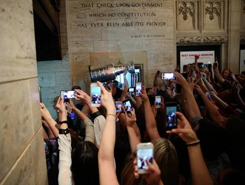 Fans surround the Stanley Cup in the lobby of Tribune Tower.