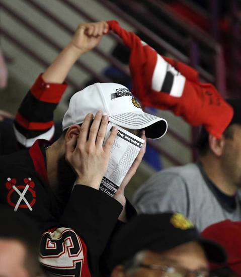 A Blackhawks fan shields his face during a stoppage in overtime in Game 2 of the Stanley Cup Final at the United Center Saturday, June 15, 2013, in Chicago. The Bruins scored to beat the Blackhawks 2-1 moments later. (John J. Kim / Chicago Tribune) B582997443Z.1 ....OUTSIDE TRIBUNE CO.- NO MAGS, NO SALES, NO INTERNET, NO TV, NEW YORK TIMES OUT, CHICAGO OUT, NO DIGITAL MANIPULATION...