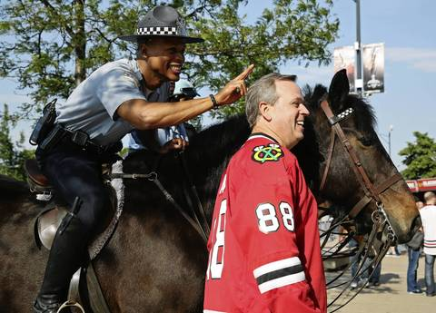 Chicago police officer Tim Hunt makes rabbit ears behind Rich Jasek, of Tinley Park, as Jasek poses for a picture next to Officer Hunt's police horse before Game 2 of the Stanley Cup Final at the United Center Saturday, June 15, 2013, in Chicago. (John J. Kim / Chicago Tribune) B582997443Z.1 ....OUTSIDE TRIBUNE CO.- NO MAGS, NO SALES, NO INTERNET, NO TV, NEW YORK TIMES OUT, CHICAGO OUT, NO DIGITAL MANIPULATION... (HOCKEY PRO CHAMPIONSHIP),FANS)