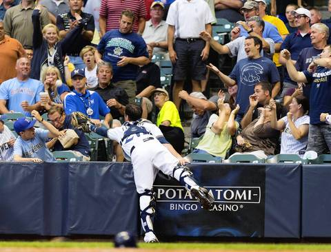 Brewers catcher Jonathan Lucroy reaches into the stands for a foul ball.