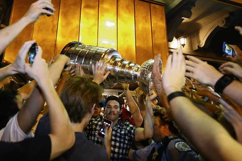 Chicago Blackhawks player Andrew Shaw is mobbed by fans while carrying the Stanley Cup leaving Market Bar on West Randolph Street, in Chicago.