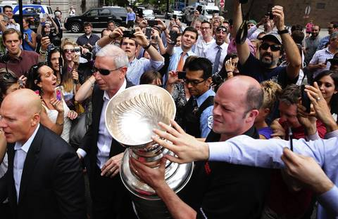 John F. McDonough, Blackhawks president and CEO, center with sunglasses, and Al Macisaac, Blackhawks vice president/assistant to the president, right, take the Stanley Cup into an event at Phil Stefani's 437 Rush as the cup tours Chicago the day after the championship.