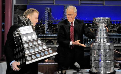 Patrick Kane holds his Conn Smythe Trophy, awarded for being the Most Valuable Player during the Stanley Cup playoffs, while Late Show host David Letterman places the Stanley Cup on his desk during Wednesday's taping in New York.