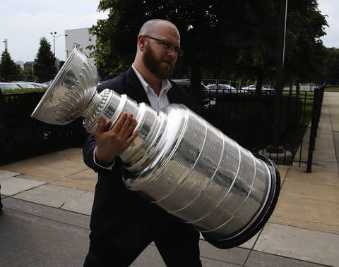 Blackhawks Senior Director for Team Services Tony Ommen carries the Stanley Cup into the United Center.