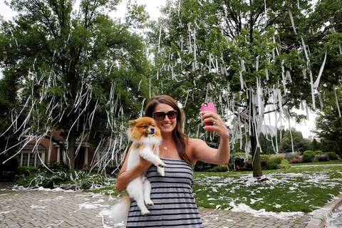 Nicole Beutler poses with her dog, Spike, in front of Joel Quenneville's TP'd home on Tuesday, in Hinsdale.