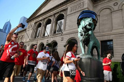 Fans on their way to the Blackhawks rally pass the Art Institute of Chicago and one of the hockey-helmet-wearing lions.