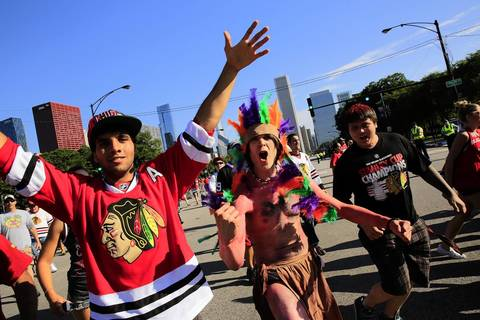 Fans wearing different types of costumes show their team loyalty as they run into Grant Park at Balbo and Columbus Avenues.