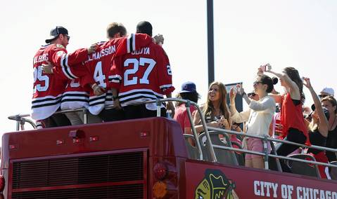 Blackhawks players are photographed by friends and relatives after boarding a parade bus at the United Center.