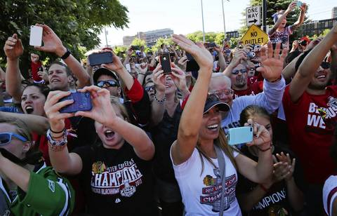 Fans cheer as the Blackhawks leave the United Center.
