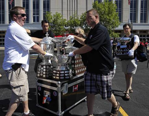 NHL trophies collected by the Blackhawks in the 2013 season, including William M. Jennings Trophy, Conn Smythe Trophy, President's Trophy, Frank J. Selke Trophy, the Clarence S. Campbell Bowl, and the Stanley Cup (inside case) are carried onto parade buses