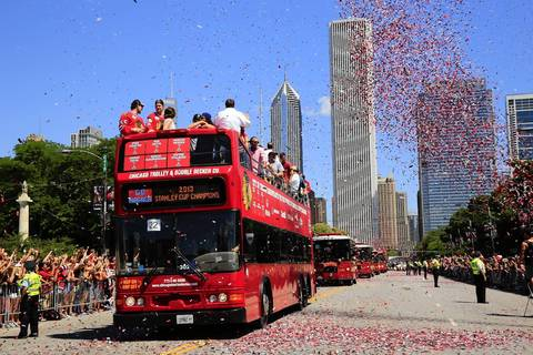 Confetti flies over buses carrying members of the Blackhawks on the way to the rally.